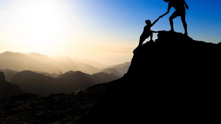 a man and a woman hiking up a mountain during a sunset where the man is helpign the woman up. this image is being used to convey the importance of working together during collaborative divorce to achieve win-win outcomes during the divorce.