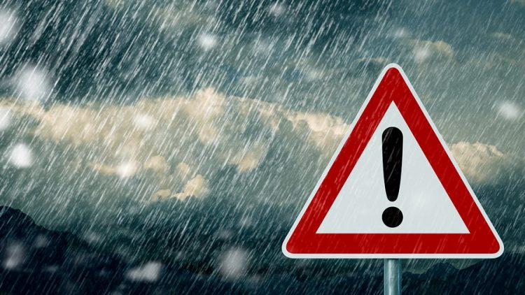a caution street sign, triangle with red outline and white border and an exclaimation mark, in the rain. this image is being used to symbolize things that you should never do during your collaborative divorce.