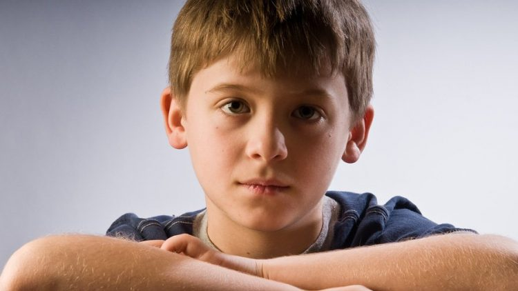 an image of a young male child looking sad or wistful. this image is being used to convey the emotional impact of divorce on younger children for a blog article on collaborative divorce