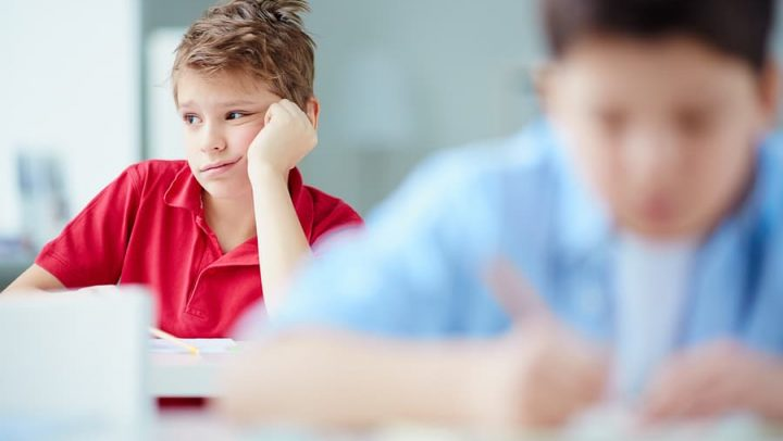 image of grade school boy sitting at his desk looking sad and distracted. this image is being used to illustrate the importance of effective communication with your grade schooler and working with ogborne law firm, a phoenix based family lawyer, during your collaborative divorce.