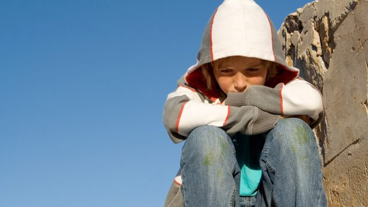 an image of a sad tween boy wearing a hoodie sitting alone framed against a blue sky. this image is being used to convey the impact of divorce on tweens and the important of understanding how to communicate with them and how ogborne law, phoenix based family law firm, can help you communicate with your tween during your collaborative divorce.