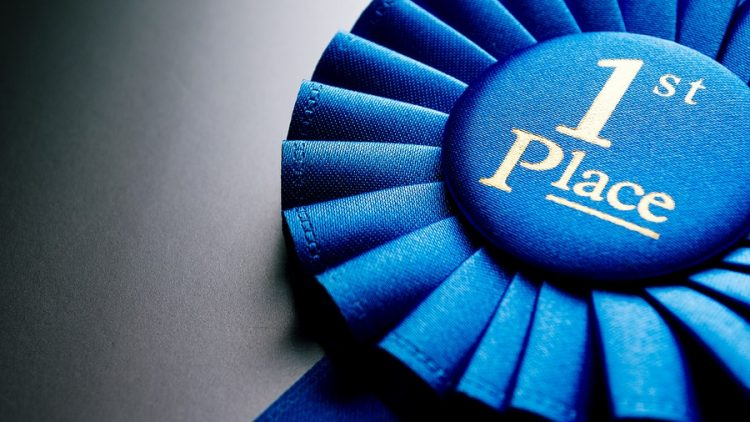 a blue ribbon award for first place. image is being used to illustrate how parents can treat parenting as a contest between them and their ex spouse as an effort to win their kids affecting during a divorce and why its important to work with ogborne law, phoenix divorce attorney, to create customized parenting plans that keep the whole family on track and winning.