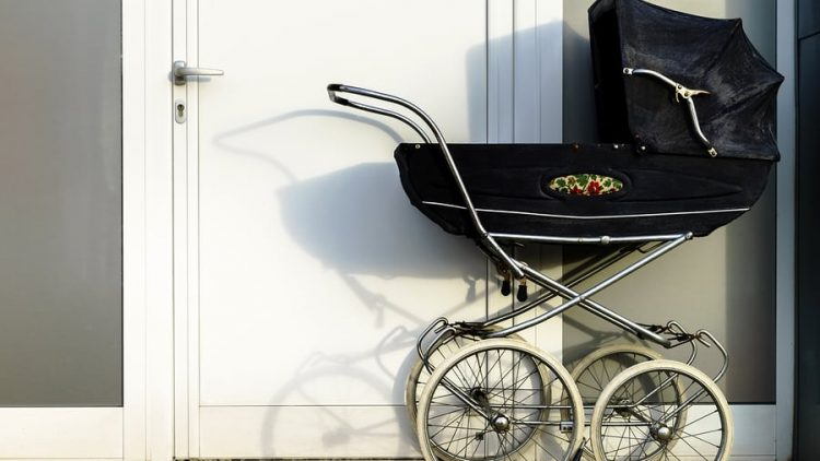 retro black baby carriage against a white door. this image is being used to convey that things like having a new baby can change your estate plan and that you need to update it by working with ogborne law, phoenix estate planning attorney.