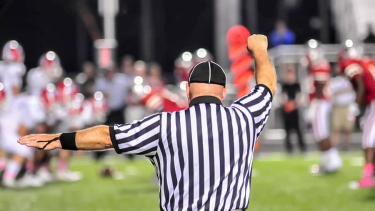 male referree at a night football game. this image is being used to represent the power of mediation in helping couples handle a divorce by engaging a neutral third party like ogborne law firm, phoenix divorce attorney, specializing in mediation and collaborative divorce.