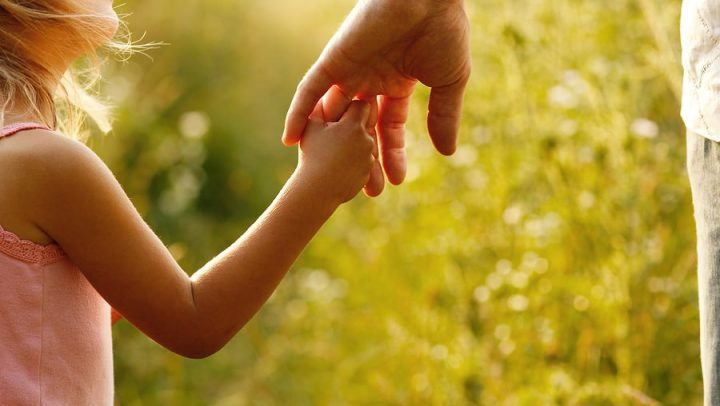 a man holding the hand of his little girl while on a walk through the tall grass. this image is being used to convey the importance of having a parenting plan in place and why ogborne law, phoenix family law firm, focuses on ensuring that you and your ex-spouse create a parenting plan that focuses on the success of the child.