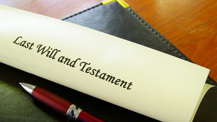 a last will and testament on a desk with a red pen. this image is being used to convey estate planning and the importance of understanding the difference between a will and a trust and why you need to work with ogborne law, phoenix estate planning attorney