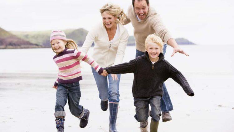 Family of four running along beach.