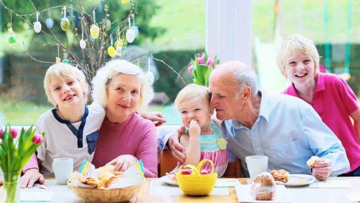 Family of 5: grandparents and grandchildren, teenage boys and toddler girl eating eggs and pastry enjoying family breakfast on Easter day sitting together in sunny kitchen with big garden view window