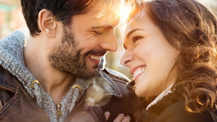 Portrait of happy young couple looking at each other and smiling outdoors.